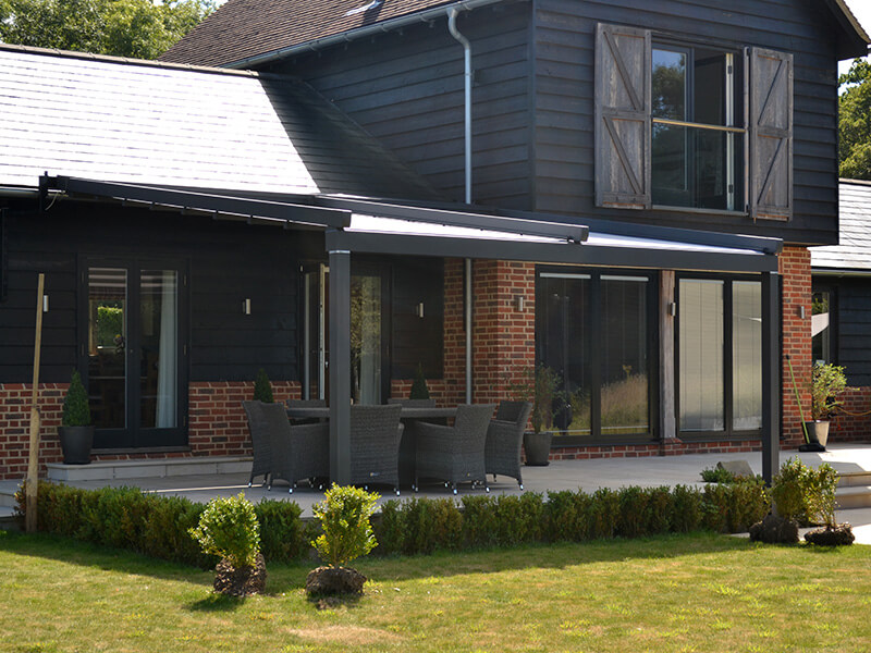 grey awning covering patio on modern barn themed house